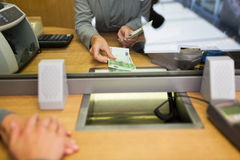Clerk giving cash money to customer at bank office. People, withdrawal, saving and finance concept - clerk giving cash money to customer at bank office or Royalty Free Stock Photography