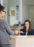 Clerk is handing over a document to a customer Royalty Free Stock Photos