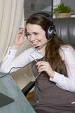 Clerk with headphones sitting in chair in office. Royalty Free Stock Photos