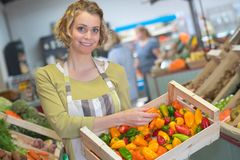 Clerk holding crate peppers Royalty Free Stock Images