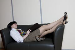clerk lying on the sofa with his legs on the back Stock Photography