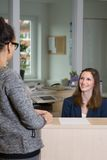 Clerk is smiling to a customer. Smiling clerk (caucasian, in the background) is sitting behind a counter and is looking to a customer (latin, in the foreground) Royalty Free Stock Photo
