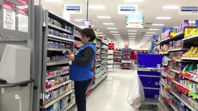 Clerk stocking medicine on shelf at pharmacy section stock video footage