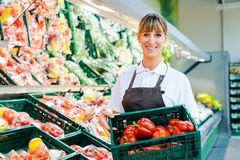 Clerk in a supermarket showing fresh vegetables. Clerk woman in a supermarket showing fresh vegetables royalty free stock photo