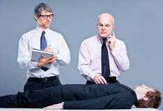 Clerks repairing a businessman for fun Stock Image