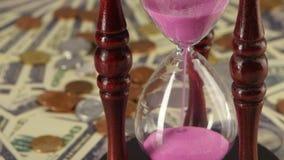 Clessidra che sta sulle monete e sulle banconote Fine in su stock footage