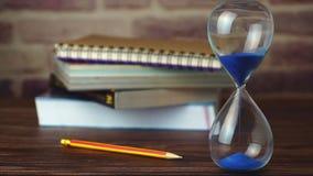 Clessidra del carrello del movimento lento con la matita ed i libri impilati sulla tavola di legno video d archivio