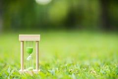 Clessidra sul campo di erba verde, tempo di molla fotografie stock libere da diritti
