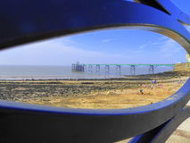 Trestle pier and beach viewed through decorative steel fence Stock Photo