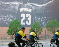 Cleveland Bike Police ride by a banner of LeBron James in downtown Cleveland, Ohio, USA royalty free stock photography