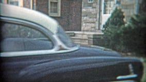 CLEVELAND, OHIO 1953: Papa die met nieuwe auto pronken die in oprijlaan trekken stock videobeelden