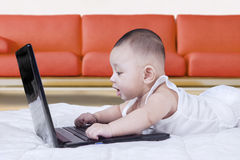 Clever baby using laptop at home Stock Photo