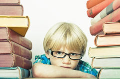 Clever boy. With a big stack of learning books royalty free stock images