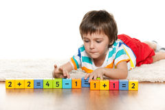 Clever boy with blocks on the carpet Stock Image