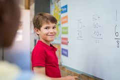 Boy doing math sum. Clever boy doing sums on white board and looking at camera. Smiling schoolboy solving addition and subtraction sum in mathematics lesson stock images