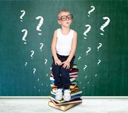 A clever boy with glasses sits on the books. A little scientist. stock image