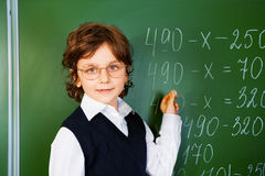 Clever boy holds chalk near blackboard Royalty Free Stock Photos