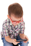 Clever boy plays with his touch smartphone Royalty Free Stock Images
