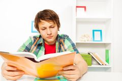 Clever boy read book sitting by table do homework Stock Photography