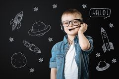 Clever boy wearing headphone ad dreaming about space flights royalty free stock photos