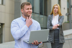 Clever businessman with laptop ahead of business lady who talking to him outdoor Royalty Free Stock Images