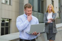 Clever businessman with laptop ahead of business lady who talking to him outdoor Stock Photos