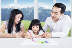 Clever child doing school task with parents Royalty Free Stock Photography