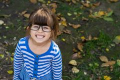 Clever child with eyeglasses smiling and looking at camera. Young pupil ready for study at school. stock photography