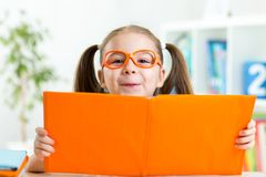 Clever child little girl behind of open book Stock Image