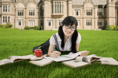 Clever Chinese student learns at park. Portrait of a clever Chinese student lying at the park while studying with books and smiling at the camera stock photos