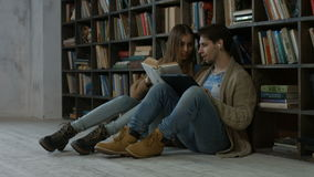 Hipster couple learning together in the library stock video footage