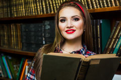 Clever female student  girl  sitting  in  library with  books. Royalty Free Stock Photos