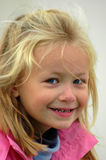 Clever girl. A beautiful white caucasian little blond girl head portrait with clever and smart expression in the pretty face smiling and watching other kids on Royalty Free Stock Image