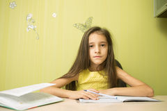 Clever girl doing homework. In his room. at the desk Royalty Free Stock Photography