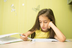 Clever girl doing homework. In his room. at the desk Royalty Free Stock Photos
