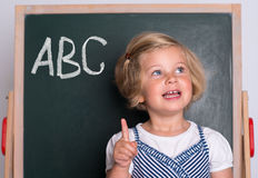 Clever girl in front of black board Royalty Free Stock Photos