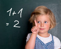 Clever girl in front of black board Stock Images