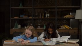 Clever girls doing homework for elementary school. Clever diverse cute girls doing homework for elementary school while sitting at desk over domestic interior stock footage