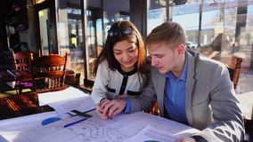 Boy helping girlfriend with architect home task drafting at cafe table. Clever guy helping pretty girlfriend with architect draft at cafe table. Charming pair stock video footage