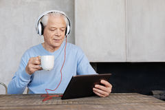 Clever handsome man employing modern technologies in his life Stock Image