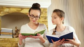 Clever and hardworking girls reading books with interest, sisters sitting together near fireplace. Children from christian family spending time after book stock video