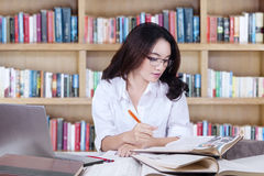 Clever high school student writing in the library Royalty Free Stock Images