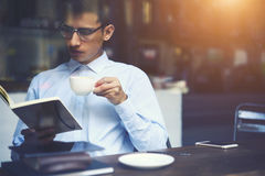 Clever hipster guy reading favourite book while enjoying tasty cappuccino. During break sitting in coffee shop. Young man in eyeglasses spending free time with Stock Photos