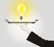 Clever idea concept with bulb on tray Royalty Free Stock Images