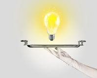 Clever idea concept with bulb on tray Royalty Free Stock Photography