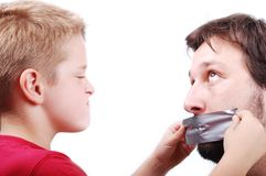 Clever kid. Clever son is putting a strip on fathers mouth Royalty Free Stock Photos