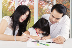 Clever kid learning with dad and mom Royalty Free Stock Photography