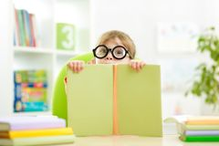 Clever kid little girl behind of open book indoor Stock Photography