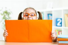 Clever kid little girl behind of open book indoor Stock Images