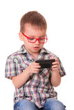Clever kid is playing with smart cell phone Royalty Free Stock Images